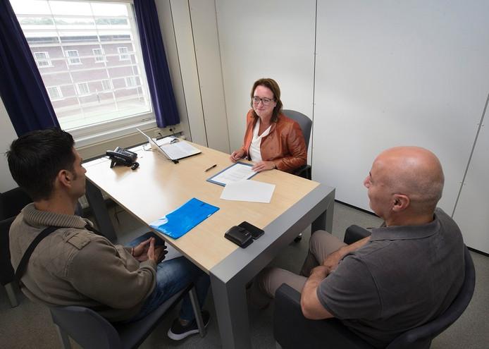 Links een vluchteling, in het midden advocate Eveline Maalsen, rechts een tolk.