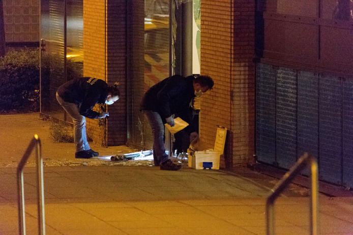 Forensisch onderzoek op de plek waar een kantoorpand is beschoten met een antitankwapen. Door de beschieting sneuvelde onder meer een raam.