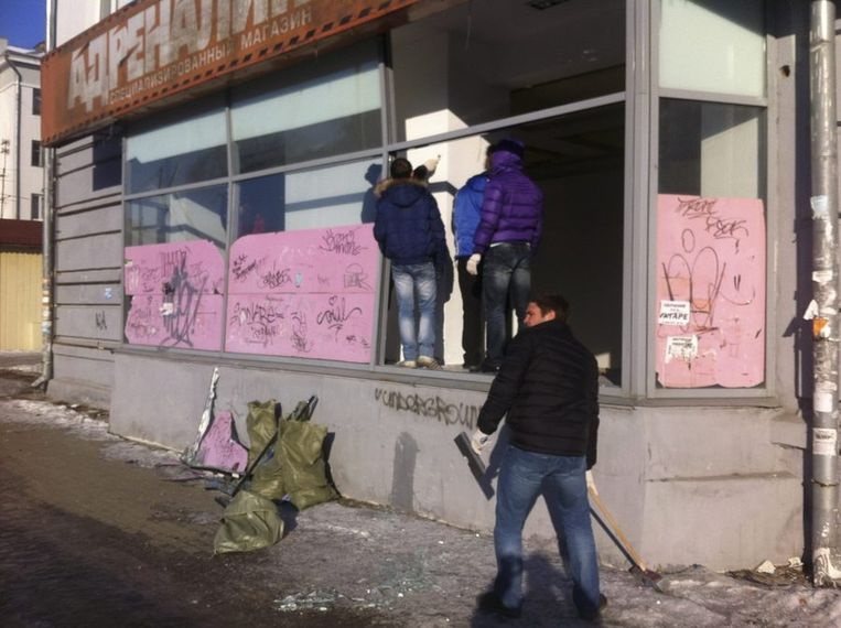 Mensen meten de schade op die een meteoriet veroorzaakt heeft in de stad Chelyabinsk.