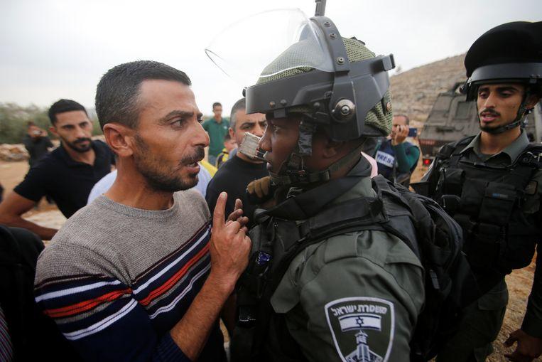 Een Palestijnse betoger in discussie met een Israëlische agent van de grenspolitie bij een demonstratie bij Hebron tegen Israëlische nederzetttingen.  Beeld Reuters