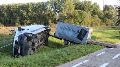 Bestelwagen met lading hout slingert gracht in