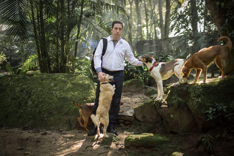 Glenn Greenwald met 4 van zijn 27 honden in zijn ommuurde tuin in Rio de Janeiro. Hij wordt streng beveiligd. Beeld Hollandse Hoogte / The New York