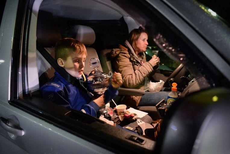 Milan Kok en zijn moeder komen terug van een kartwedstrijd (Milan werd derde). Eten in de auto, eens in de veertien dagen, vinden ze lekker warm en snel. Beeld Marcel van den Bergh