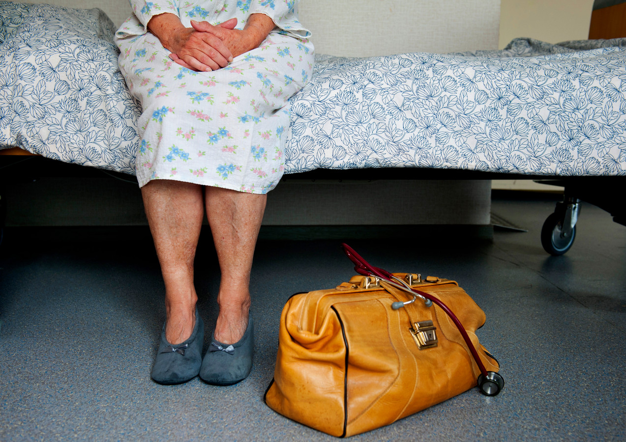 Een oudere dame in nachtpon zit op bed tijdens doktersbezoek. Foto ter Illustratie