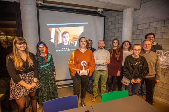 Centraal Pen Stewart met de trofee voor de winnaar die live op het scherm te zien, samen met de andere deelnemers en juryleden.