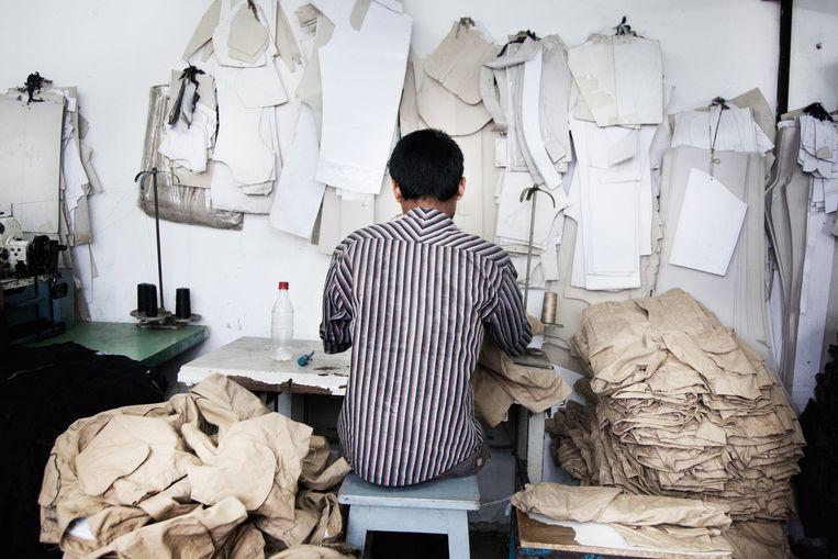 Een man aan het werk op de naaiafdeling van Tracker Fashion Beeld null