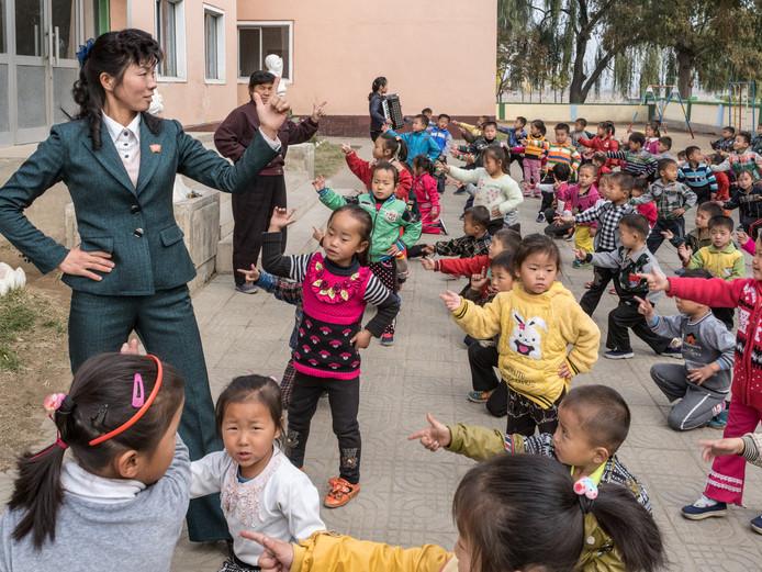Lesgevers leren Kindergarten-studenten dansen; Chongsan-ri Cooperative Farm. © Carl De Keyzer / Magnum Photos. ED 14 juni 2018. Hoofdfoto.