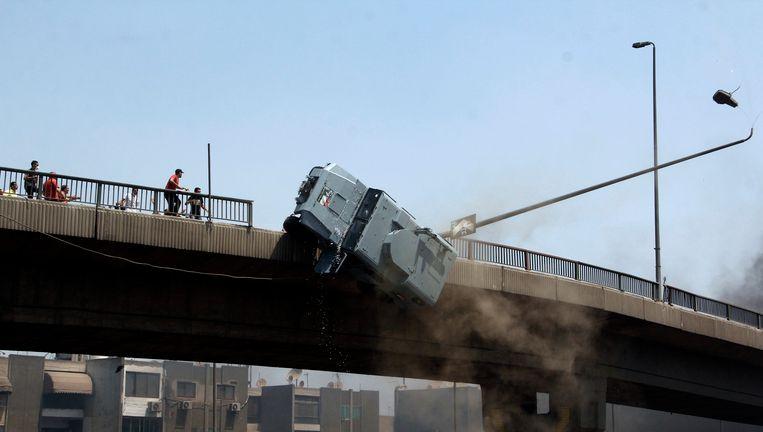 Een politievoertuig wordt van een brug geduwd in Nasr City in Caïro. Beeld ap