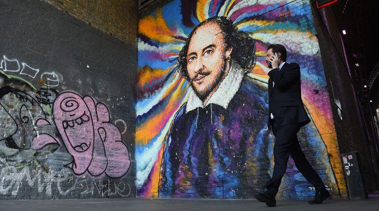 Een man loopt langs een muurschildering van William Shakespeare in Londen, gemaakt door graffiti-artiest James Cochran. Beeld EPA