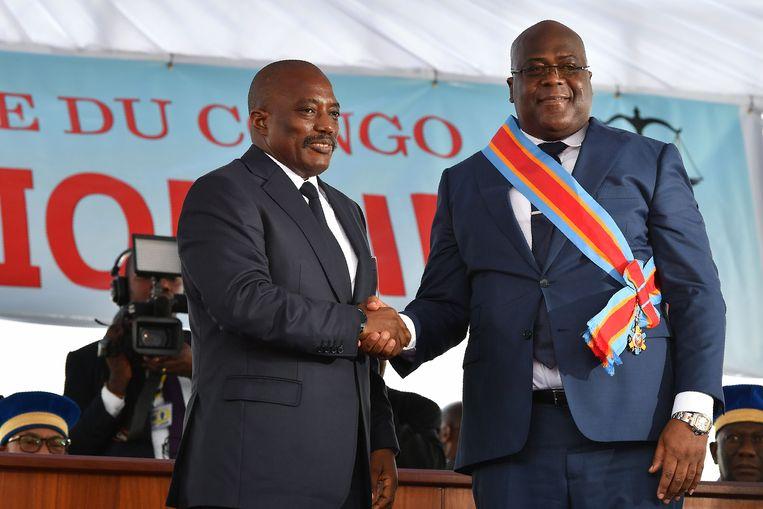 Voormalig president Joseph Kabila schudt handen met de zojuist beëdigde president Félix Tshisekedi.  Beeld AFP
