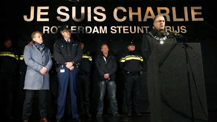 Burgemeester Ahmed Aboutaleb houdt een toespraak tijdens een demonstratie naar aanleiding van de aanslag in Parijs. Links hoofdredacteur Christiaan Ruesink van het Algemeen Dagblad en korpschef Frank Pauw.
