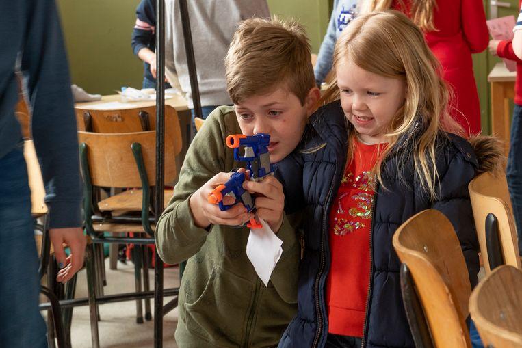 Deze jongen wil soldaat worden en toont aan een meisje hoe hij dat wil doen.