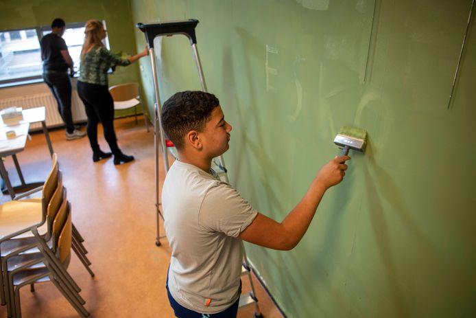 Rofino schildert een muur in een lokaal van Track013