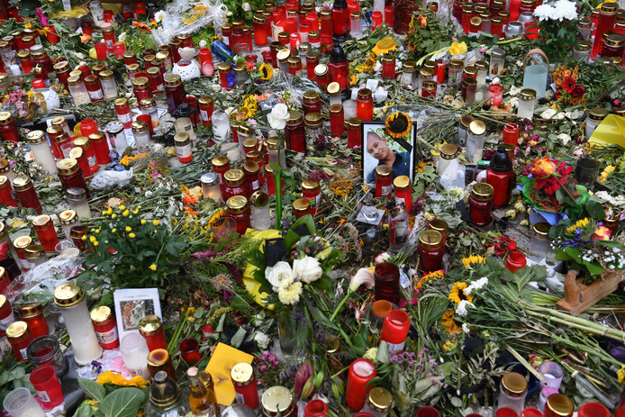 Een foto van het 35-jarige slachtoffer omringd door bloemen en kaarsjes.