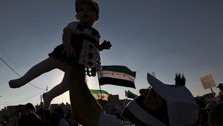 Een Syrische demonstrant in Jordanië tilt een kind op. Beeld reuters