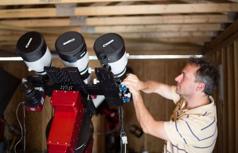 Pieter van Dokkum bij een Dragonfly-testopstelling met drie lenzen. Beeld Dragonfly