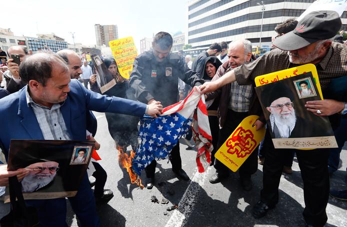 Iraanse betogers steken in Teheran een Amerikaanse vlag in brand.
