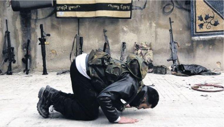 Een lid van het Vrije Syrische Leger bidt in de straten van Aleppo. Beeld reuters