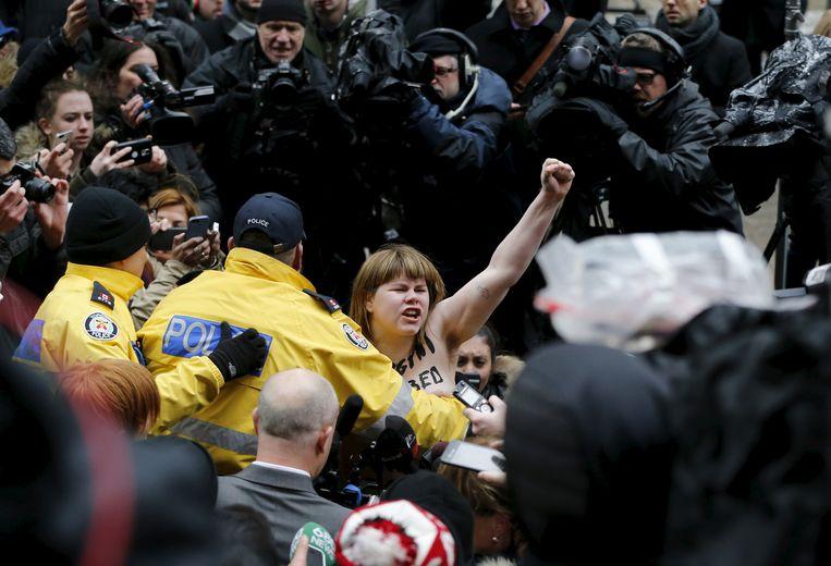 Een topless vrouw wordt aangehouden als ze protesteert tegen de vrijspraak van Jian Ghomeshi, die werd beticht van seksueel geweld. Beeld Reuters