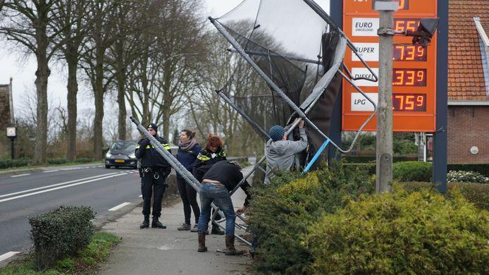 Bewoners en agenten halen een trampoline weg bij een tankstation aan de Provincialeweg West in Haastrecht.