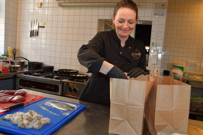 """Klaar voor een nieuwe ronde. Nicolette Meesen pakt gerechten in voor thuisbezorging. ,,Van alle lieve reacties krijgen we energie."""""""
