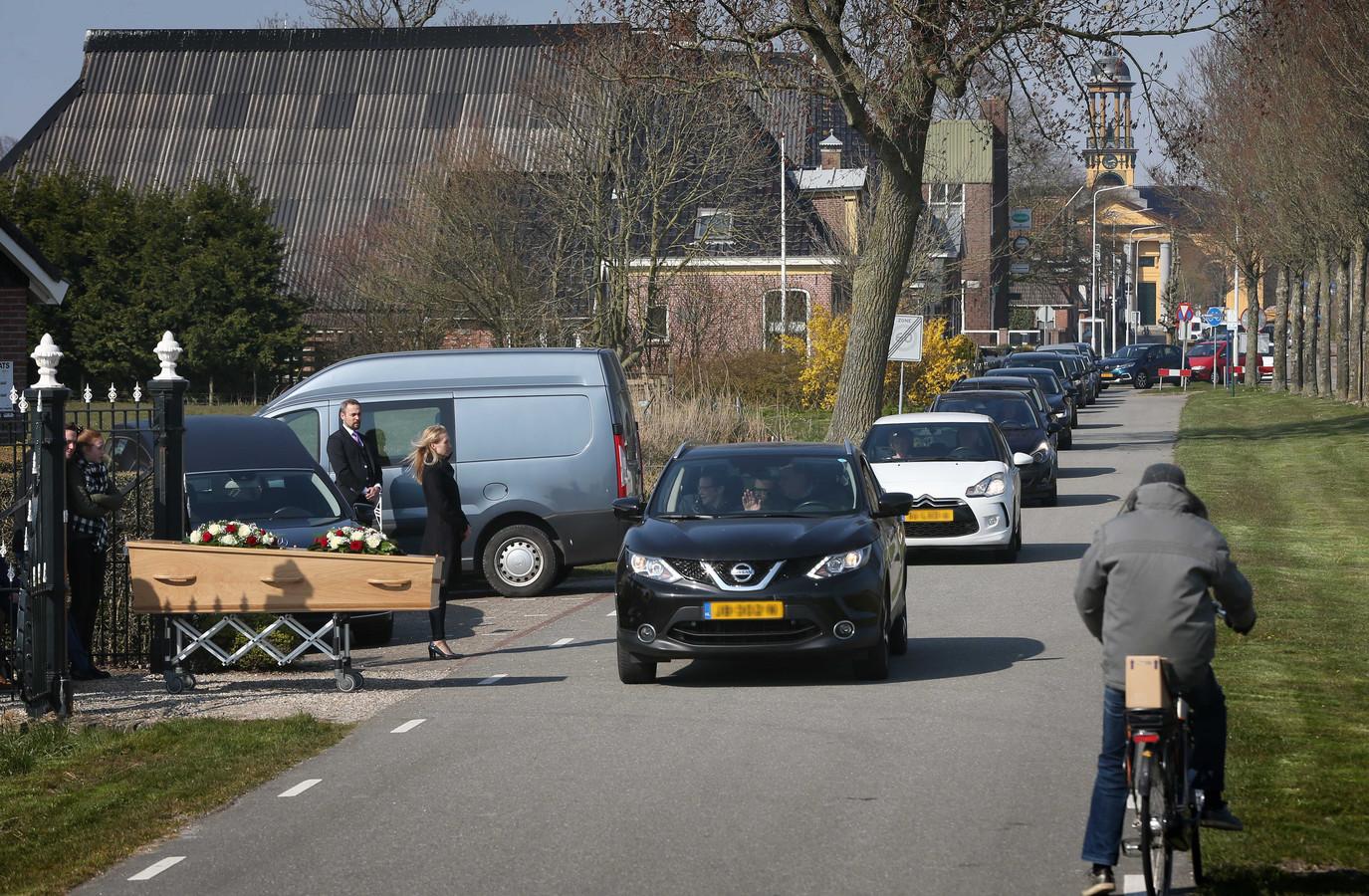 Nabestaanden nemen vanuit de auto afscheid van de overledene. Wegens de coronacrisis zijn er niet meer dan 30 mensen welkom bij begrafenissen.
