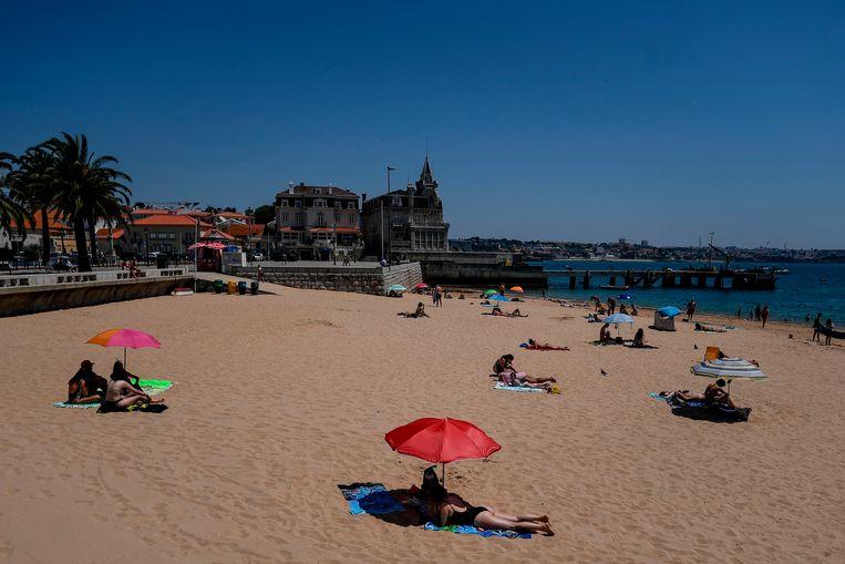 Mensen aan het zonnebaden in Lissabon, Portugal. Beeld AFP