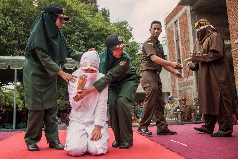 Links: Saydiah (28), beschuldigd van overspel, vlak voor ze twintig zweepslagen krijgt in Lhong Raya, Banda Atjeh.  Beeld Rony Zakaria