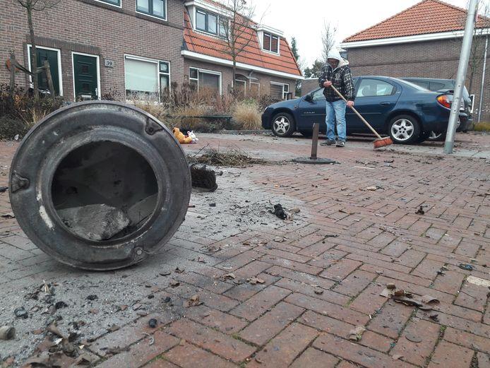 Een buurman veegt de plek schoon, waar een man uit Enschede vlak na middernacht als gevolg van een vuurwerkexplosie overleed.