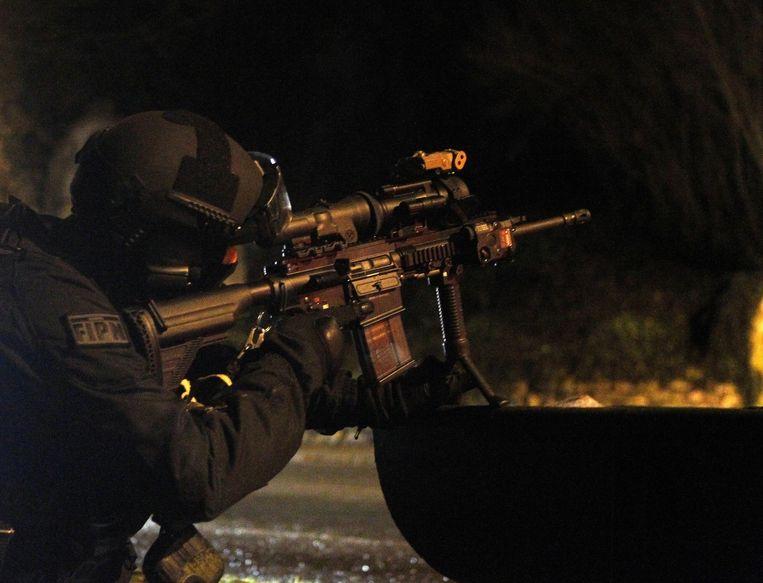 Een Franse politieagent kijkt door de loep van zijn geweer in Fleury. Beeld ap