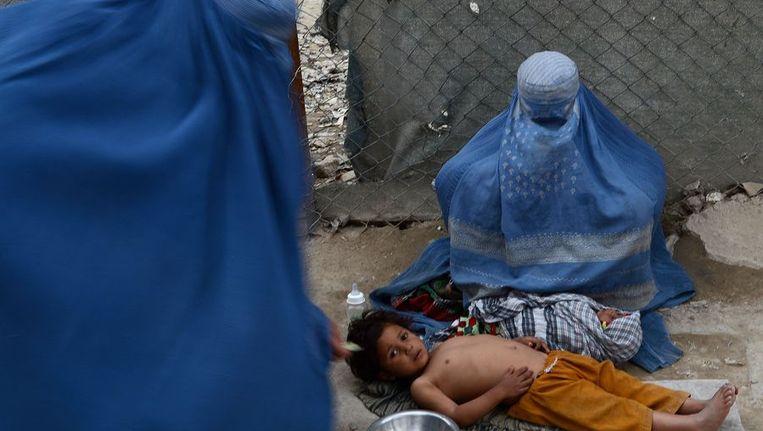 Een Afghaanse vrouw met haar kind bedelt op straat tijdens Nowruz. Beeld afp