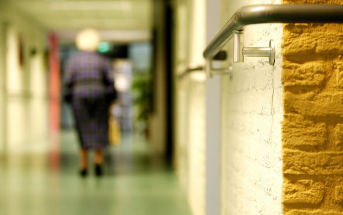 Foto ter illustratie. Bewoner van verpleeghuis loopt met rollator op gang.