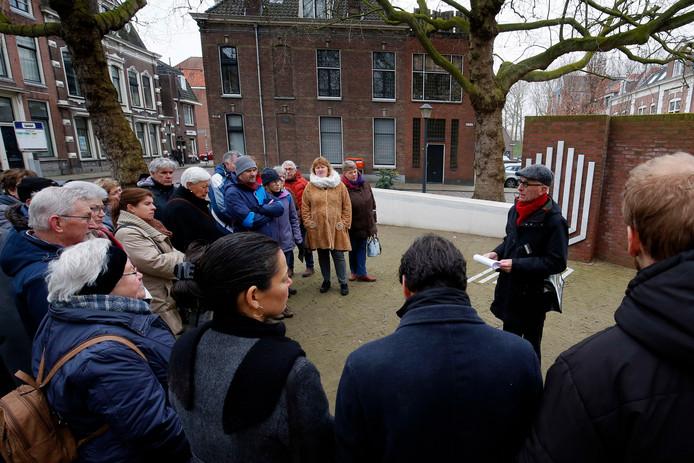 Stadsgids Dick Bosch neemt een groep mensen mee voor een wandeling langs historische locaties met een link naar de Tweede Wereldoorlog.