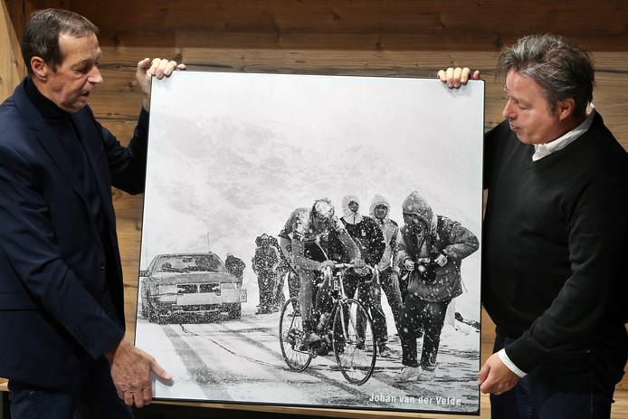 Johan van der Velde (links)  en John van Ierland kijken naar de legendarische actiefoto van Van der Velde in de sneeuw tijdens de Ronde van Italië van 1988, waar hij de bijnaam L'uomo di Gavia aan dankt.
