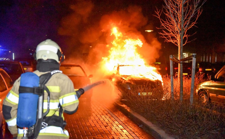 De brandweer blust een autobrand aan de Zamenhofdreef in Overvecht. Een camerapaal bedoeld om dit soort branden te voorkomen is nu zelf in brand gestoken.