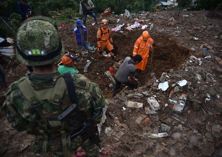 Reddingswerkers zoeken naar overlevenden in de modder.
