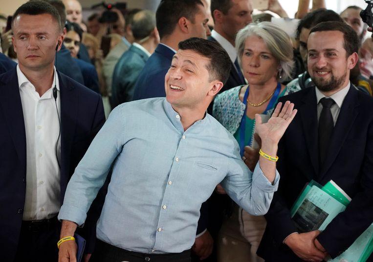 De Oekraïense president Volodymir Zelenski gebaart terwijl hij aankomt aan bij een stembureau in Kiev.  Beeld AP