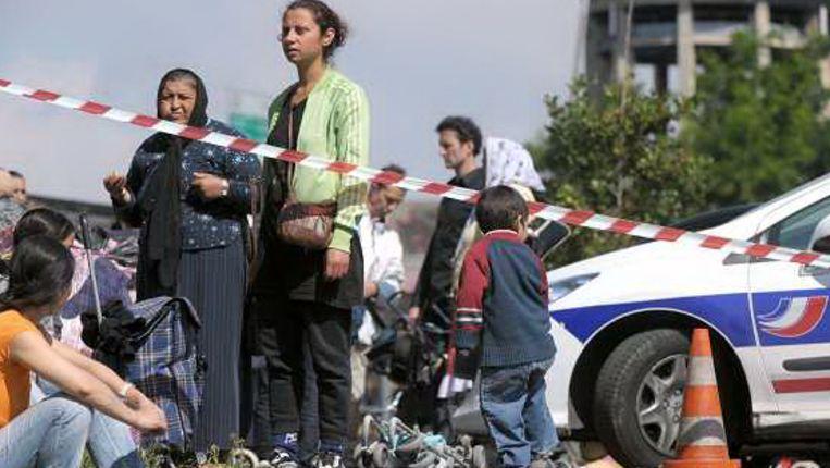 Zigeuners kijken toe hoe de Franse autoriteiten hun kamp ontruimd. (AEP) Beeld
