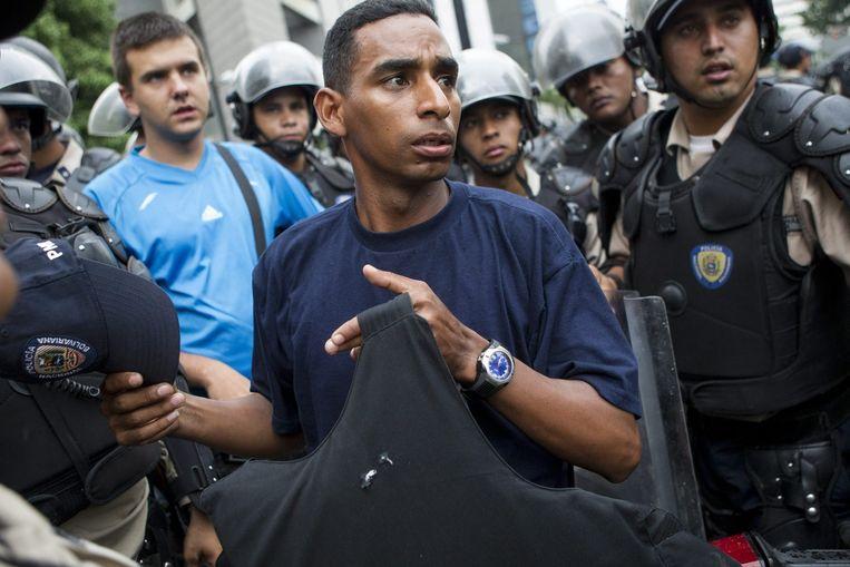 Een agent toont zijn kogelwerend vest nadat hij is beschoten. Beeld epa