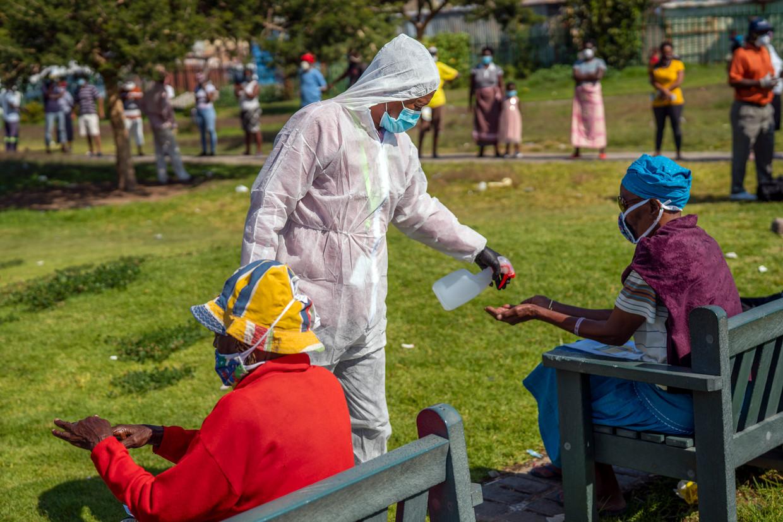 Op een testlocatie in het township Diepsloot, waar inwoners op het coronavirus worden getest, krijgen mensen desinfecterende spray op hun handen gespoten. Veel inwoners willen niet worden getest.