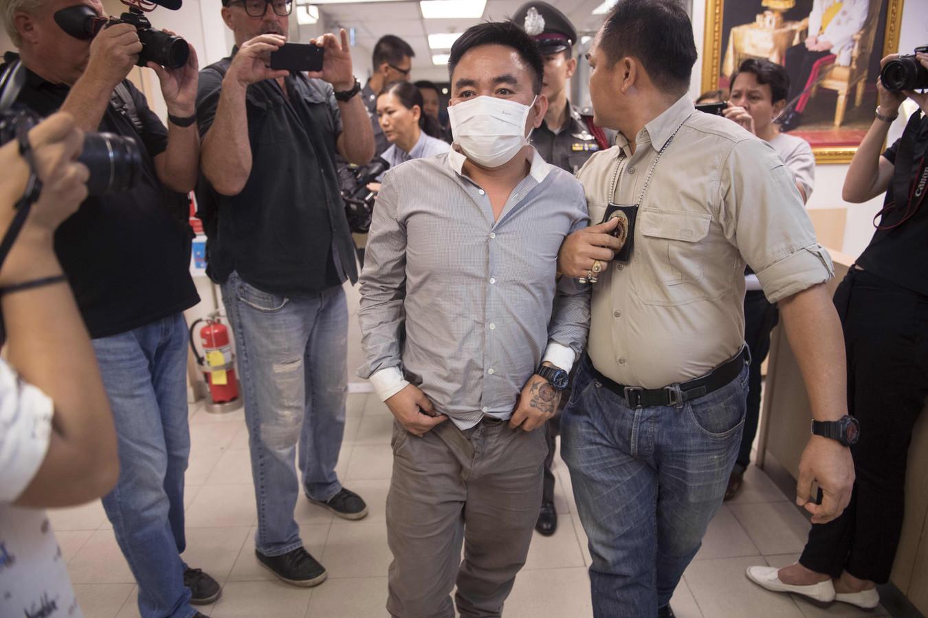 Boonchai Bach wordt onder grote aandacht van de media naar een politiebureau in Bangkok gebracht.