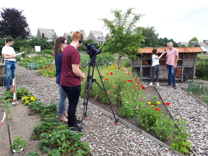 Filmen voor campagne 'De Orde van de Klauw' in buurttuin de Biezen, Ussen. Links Daan, rechts, naast Marcel Stokenbrook, Sarah.