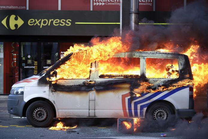 Twee politiebusjes werden in brand gestoken en gingen in vlammen op.