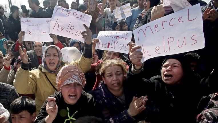 Vluchtelingen aan de grens tussen Griekenland en Macedonië vragen de Duitse bondskandelier Merkel om hulp. Beeld epa