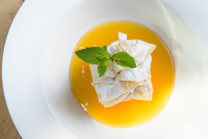 Nagerecht: Fleur d'Amour. Vanille-ijs in een krokant pakketje van filodeeg met een pasta van zuidvruchten, noten en specerijen. Geserveerd met sinaasappelsaus.