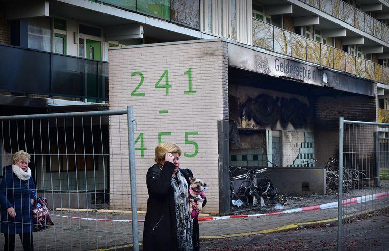 Buurtbewoners passeren in Arnhem de plaats waar in de nieuwjaarsnacht brand heeft gewoed, als gevolg waarvan twee doden vielen.  Beeld Marcel van den Bergh / de Volkskrant