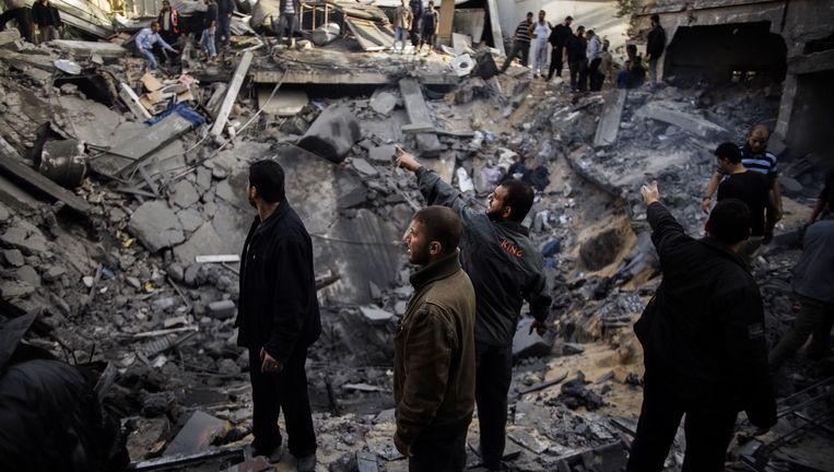 Palestijnen staan rond een krater in een woonwijk die is veroorzaakt door een Israëlische raketinslag. Beeld AFP