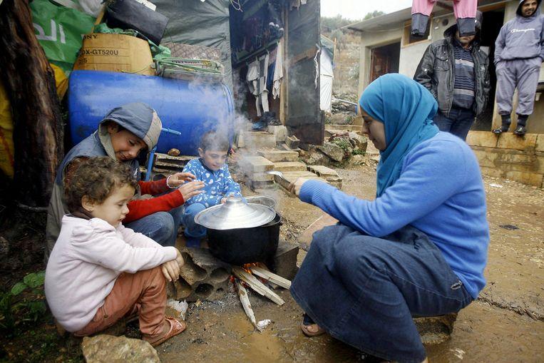 Een Syrische vrouw maakt eten klaar in een vluchtelingenkamp. Beeld ap