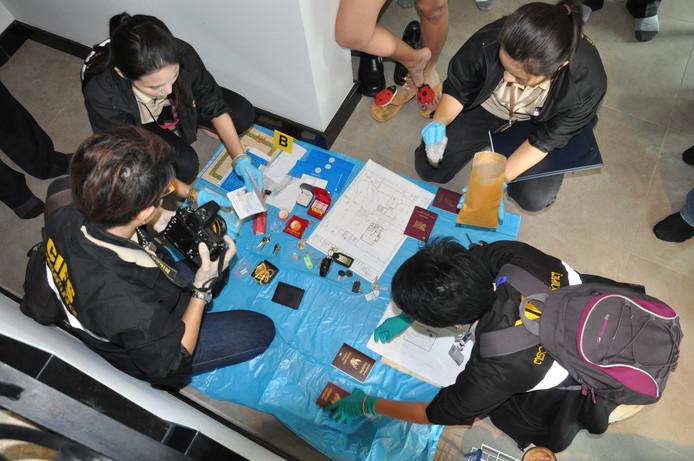 Thaise politiemensen buigen zich over de spullen die zijn gevonden bij de inval in de woning van Johan van Laarhoven