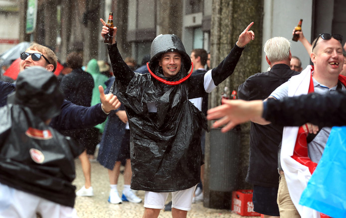 De Engelse supporters vermaken zich wel in de stromende regen.
